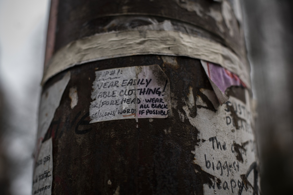"An electric post covered in stickers, including a tip for protesters to ""wear all black"" is seen near Chapman Square, in downtown Portland, Oregon, on January 30, 2021. The square is a common site for protests, due to its proximity to the Multnomah County Justice Center and the Mark O. Hatfield Federal Courthouse."