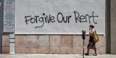 A woman wearing a mask walks past a wall bearing a graffiti asking for rent forgiveness on La Brea Ave on National May Day amid the Covid-19 pandemic, May 1, 2020, in Los Angeles, California. - Several cities and states, including California, have passed executive orders prohibiting eviction of tenants affected by the coronavirus crisis.But when the lockdown lifts, the moratorium will end. And tenants will have to pay their back-rent or move out. (Photo by VALERIE MACON / AFP) (Photo by VALERIE MACON/AFP via Getty Images)