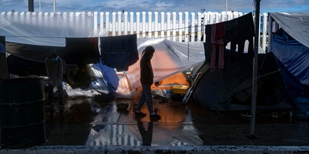 A migrant girl walks at an improvised camp outside El Chaparral crossing port as they wait for US authorities to allow them to start their migration process in Tijuana, Baja California state, Mexico, on March 11, 2021. - President Biden's administration moved quickly to start dismantling the controversial ¬remain in Mexico policy, officially called the Migrant Protection Protocols (MPP), with a first stage that began on February 2021, while thousands of migrants out of MPP program are stranded along the US-Mexico border without knowing when or how they will be able to start their migratory process with US authorities. (Photo by Guillermo Arias / AFP) (Photo by GUILLERMO ARIAS/AFP via Getty Images)
