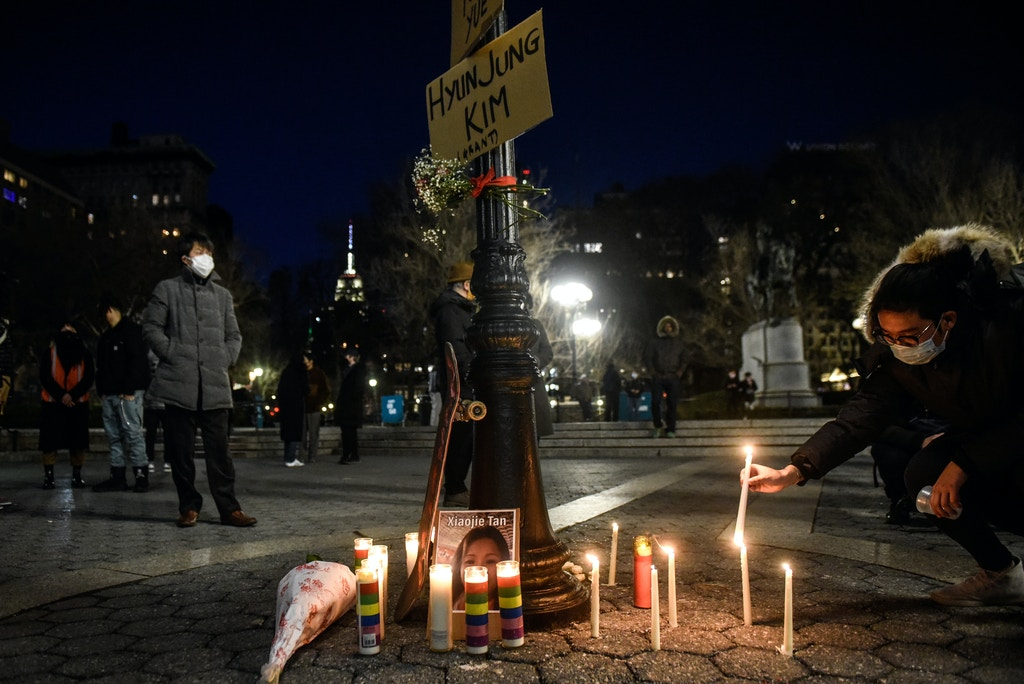 A person lights candles during a peace vigil to honor victims of attacks on Asians on March 19, 2021 in Union Square Park in New York City.
