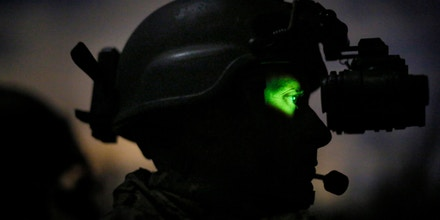 STENNIS SPACE CENTER, MS - FEBRUARY 20: An active-duty Special Boat Team member from the Navy's riverine Gulf Coast team peers through a night vision device while patrolling the Pearl River on a night training operation on February 20, 2013 in the swamps of the John C. Stennis Space Center in Stennis Space Center, Mississippi. Special Warfare Combatant-Craft Crewmen, or SWCCs, are members of the United States Navy's Special Boat Teams and are responsible for insertion, extraction, and combat fire support for the U.S. Navy SEALs. Ninety percent of riverine training takes place at night, due to the enormous advantage afforded to American special operations forces because of their extensive night vision capabilities.(Photo by Luke Sharrett/Getty Images)