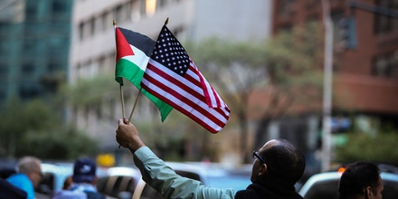 MANHATTAN, NEW YORK CITY, NEW YORK, UNITED STATES - 2015/10/06: US & Palestinian flags held aloft. Al Awda, NYC Students for Justice in Palestine and other activists organizations staged a
