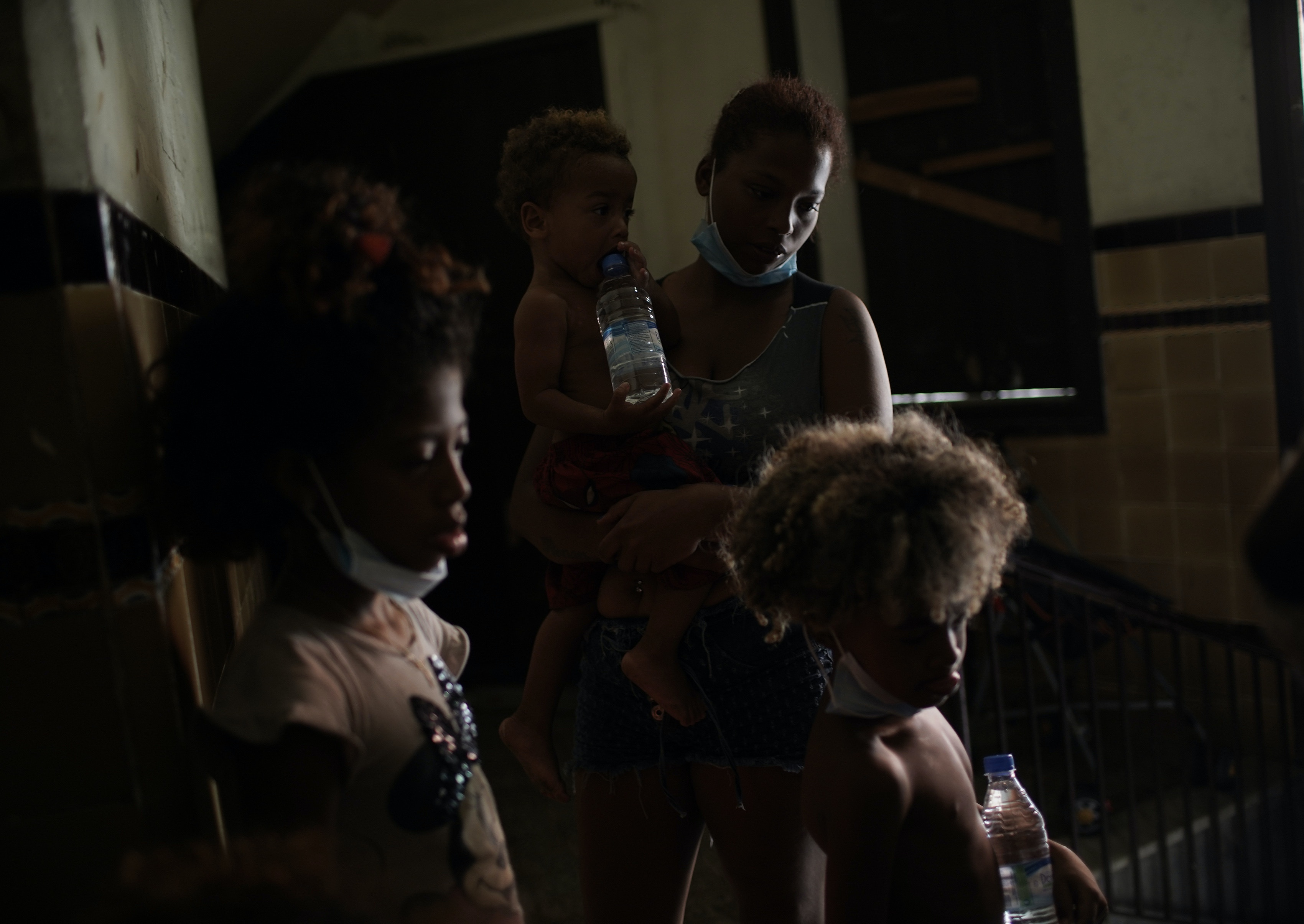 Residents wait to be served a plate of food donated by aid groups, inside an occupied building amid the new coronavirus pandemic, in Rio de Janeiro, Brazil, on March 10, 2021.