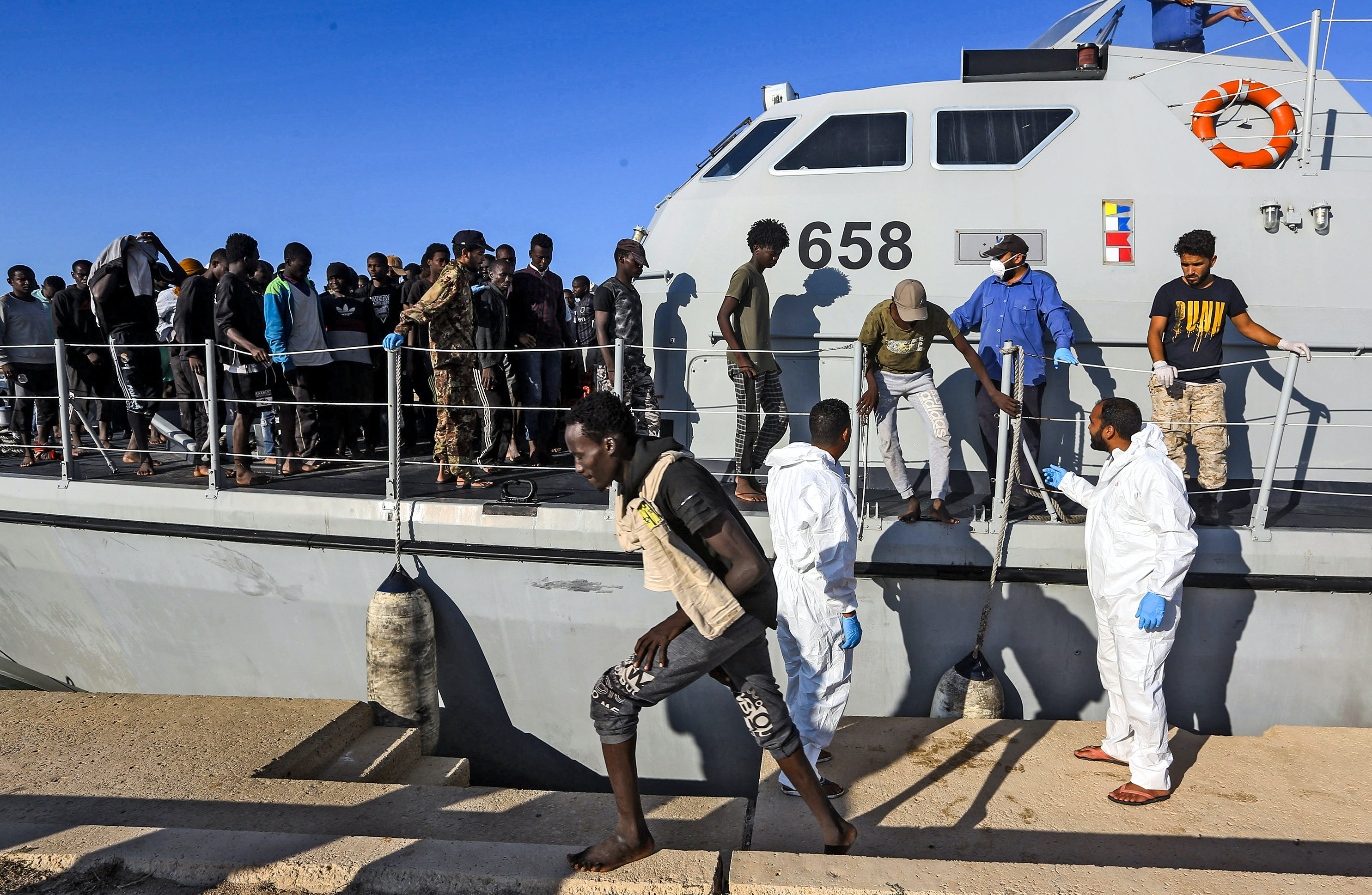 Rescued migrants disembarking from a Libyan coast guard ship in the town of Khoms, a town 120 kilometres (75 miles) east of the capital on October 1, 2019.