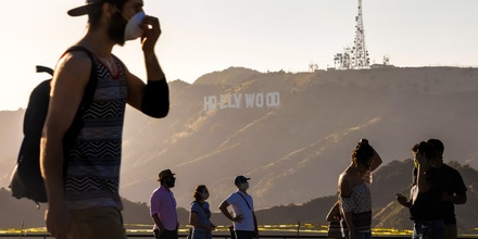 People wearing facemasks walk at the Griffith Observatory with a view of the Hollywood sign at the start of Memorial Day holiday weekend amid the novel coronavirus pandemic in Los Angeles on May 22, 2020. (Photo by Apu GOMES / AFP) (Photo by APU GOMES/AFP via Getty Images)