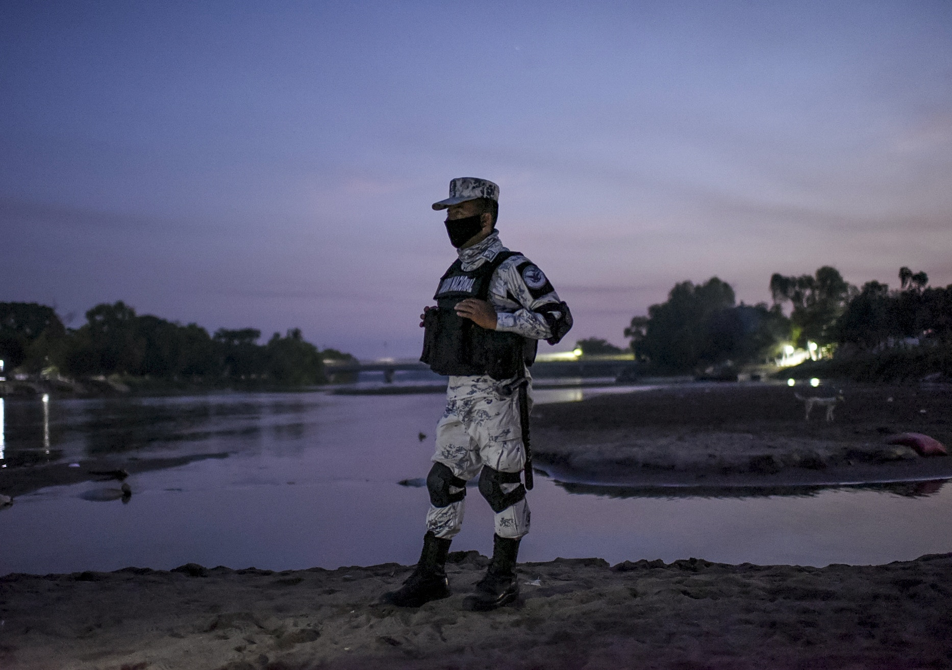 "TOPSHOT - An officer of the National Guard of Mexico stand guard at the banks of the Suchiate River in Ciudad Hidalgo, Chiapas state, Mexico, border with Tecun Uman, Guatemala, on January 19, 2021. - The Mexican government said it would not allow the ""illegal entry"" of any migrant caravans and has deployed 500 immigration officers to the border states of Chiapas and Tabasco. (Photo by Isaac GUZMAN / AFP) (Photo by ISAAC GUZMAN/AFP via Getty Images)"
