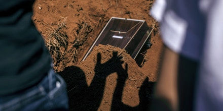 Mourners watch as workers wearing protective equipment bury the casket of a Covid-19 victim at the Vila Formosa cemetery in Sao Paulo, Brazil, on Wednesday, March 24, 2021. Brazil reported more than 3,000 Covid-19 deaths for the first time in a 24-hour period on Tuesday, as the pandemic spreads unchecked across Latin Americas biggest economy and the nation approaches 300,000 lives taken. Photographer: Victor Moriyama/Bloomberg via Getty Images