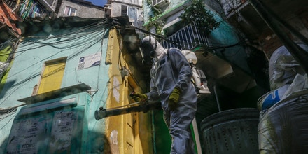 A worker wearing personal protective equipment (PPE) performs disinfection operations at Dona Marta favela in Rio de Janeiro, Brazil, on Saturday, March 27, 2021. Staggering under its worst period of the pandemic, with daily records of caseloads and deaths, Brazil is facing a daunting development: a rising number of deaths among the young. Photographer: Andre Coelho/Bloomberg via Getty Images