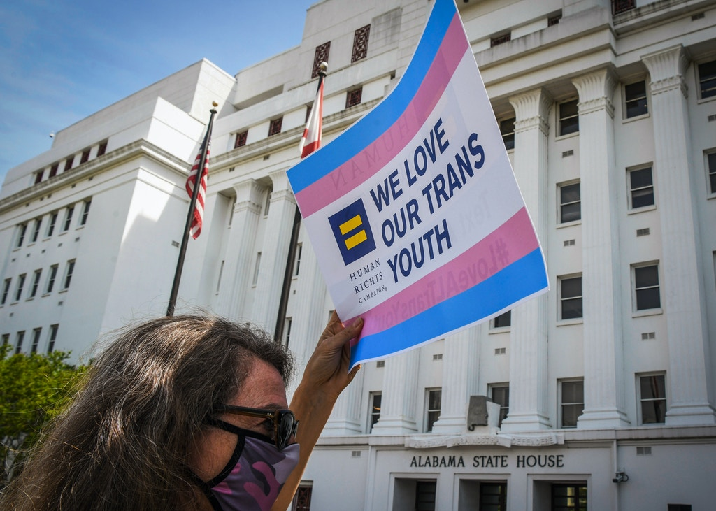 "MONTGOMERY, AL - MARCH 30: Jodi Womack holds a sign that reads ""We Love Our Trans Youth"" during a rally at the Alabama State House to draw attention to anti-transgender legislation introduced in Alabama on March 30, 2021 in Montgomery, Alabama. There are so far 192 anti-LGBTQ bills under consideration in state legislatures across the United States. Of those, 93 directly target transgender people. (Photo by Julie Bennett/Getty Images)"
