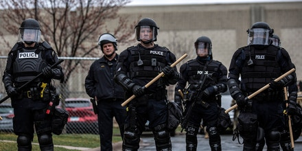 Minnesota Police officers stand guard outside the Brooklyn Center Police Station after a police officer shot and killed a Black man in Brooklyn Center, Minneapolis, Minnesota on April 12, 2021. - A suburb of Minneapolis was under curfew early April 12, 2021 after US police fatally shot a young Black man, sparking protests not far from where a former police officer was on trial for the murder of George Floyd.Hundreds of people gathered outside the police station in Brooklyn Center, northwest of Minneapolis, with police later firing teargas and flash bangs to disperse the crowd, according to an AFP videojournalist. (Photo by Kerem Yucel / AFP) (Photo by KEREM YUCEL/AFP via Getty Images)