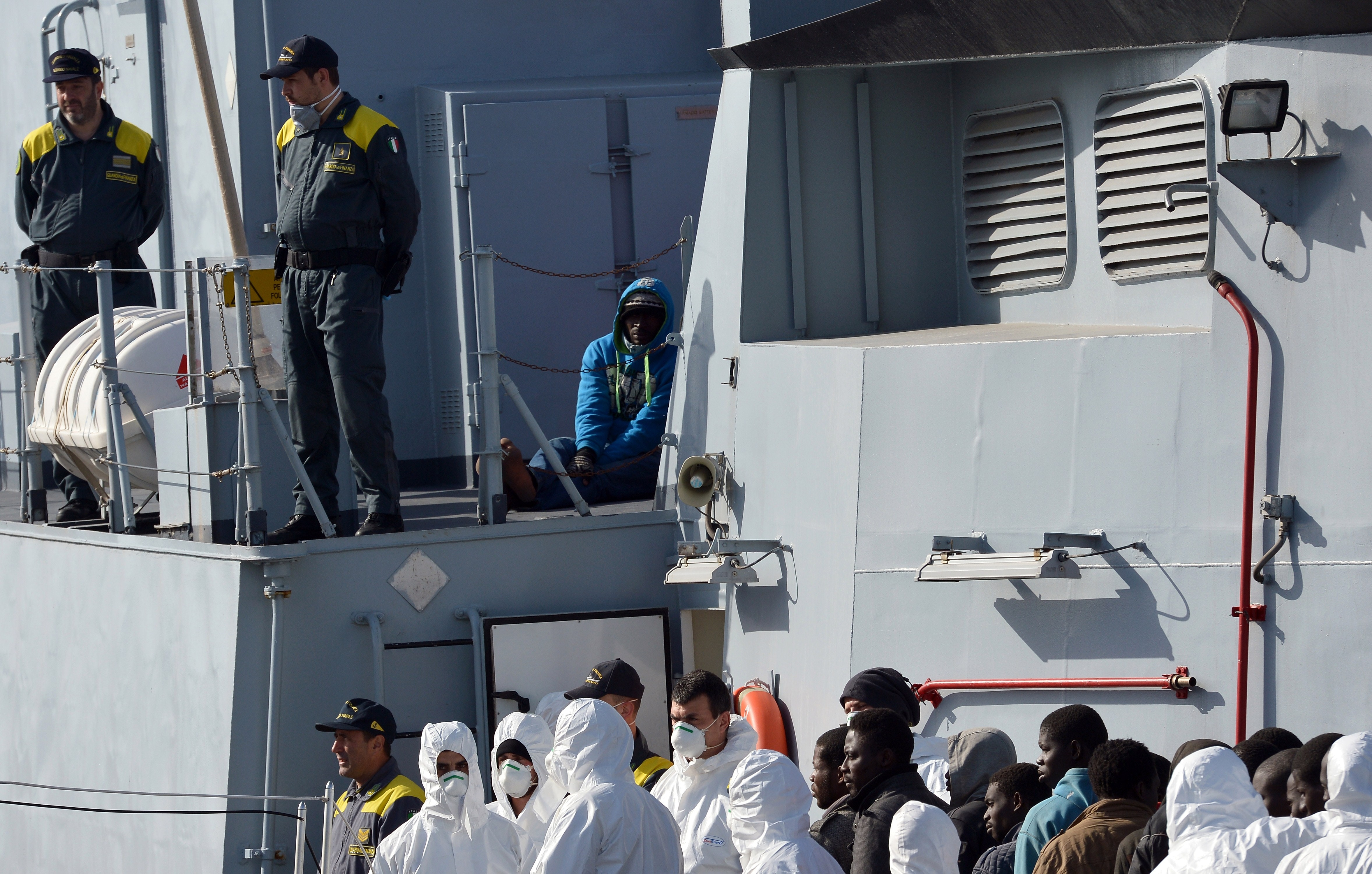 Italian police stand next to a migrant suspected to be a smuggler (up-R) as they disembark off rescued migrants from the Italian Guardia di Finanza vessel Denaro at the Sicilian harbour of Catania on April 23, 2015.