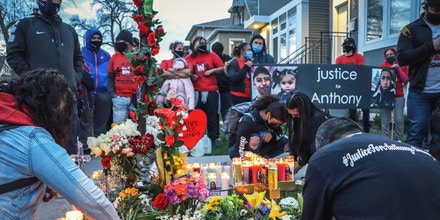 Roxana Figueroa, left, tends to a memorial laid in honor of her cousin, 22-year-old Anthony Alvarez, in the Portage Park neighborhood of Chicago on April 23, 2021.