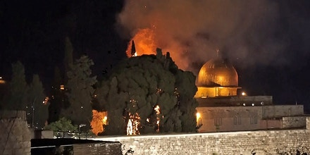 A grab from an AFPTV video shows a tree on fire near the Dome of the Rock mosque in Jerusalem's Al-Aqsa mosque complex on May 10, 2021, following renewed clashes between Palestinians and Israeli police at the scene. (Photo by Claire GOUNON / AFPTV / AFP) (Photo by CLAIRE GOUNON/AFPTV/AFP via Getty Images)