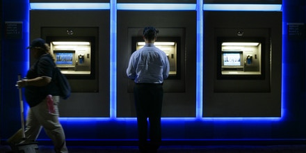 A man uses the Chase ATM machine at the U.S. Tennis Center in New York, NY on Thursday, Sept. 8, 2005.  JPMorgan Chase & Co., the nation's third biggest banking company, reported Wednesday, Oct. 19, 2005, that strength in investment banking, including record trading revenue, contributed to a 78 percent increase in third-quarter profits.  (AP Photo/Amy Sancetta)