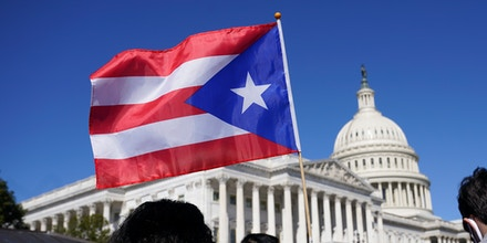 A woman waves the flag of Puerto Rico during a news conference on Puerto Rican statehood on Capitol Hill in Washington, on March 2, 2021.