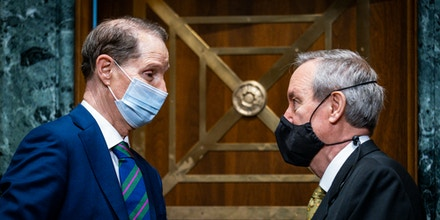 Sen. Ron Wyden, D-Ore., left, talks with Sen. Mike Crapo, R-Idaho, before the Senate Finance Committee, on May 12, 2021 on Capitol Hill in Washington.