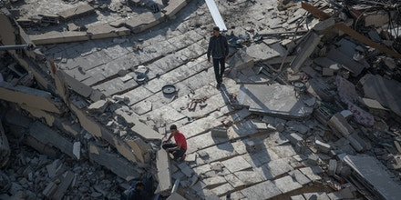 Palestinians inspect the rubble of their destroyed home after being hit by Israeli airstrikes in town of Beit Lahiya, northern Gaza Strip, on May 13, 2021.