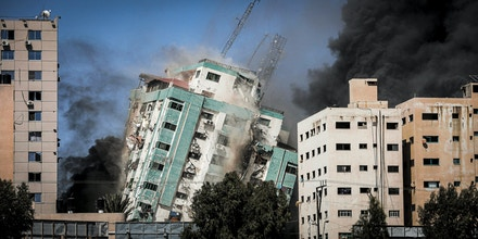 A ball of fire erupts from the Jala Tower as it is destroyed in an Israeli airstrike in Gaza city controlled by the Palestinian Hamas movement, on May 15, 2021. - Israeli air strikes pounded the Gaza Strip, killing 10 members of an extended family and demolishing a key media building, while Palestinian militants launched rockets in return amid violence in the West Bank. Israel's air force targeted the 13-floor Jala Tower housing Qatar-based Al-Jazeera television and the Associated Press news agency (Photo by Momen Faiz/NurPhoto via AP)