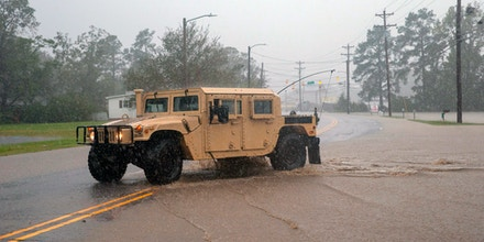 A military vehicle crosses a flooding road as workers scramble to build a temporary dam to stop rising flood waters from Hurricane Florence in Lumberton, North Carolina, on September 16, 2018.