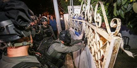 Israeli soldiers force the gate of a Palestinian family's home as Palestinians gather to protest the forced displacements in the Sheikh Jarrah neighborhood in East Jerusalem on May 6, 2021.