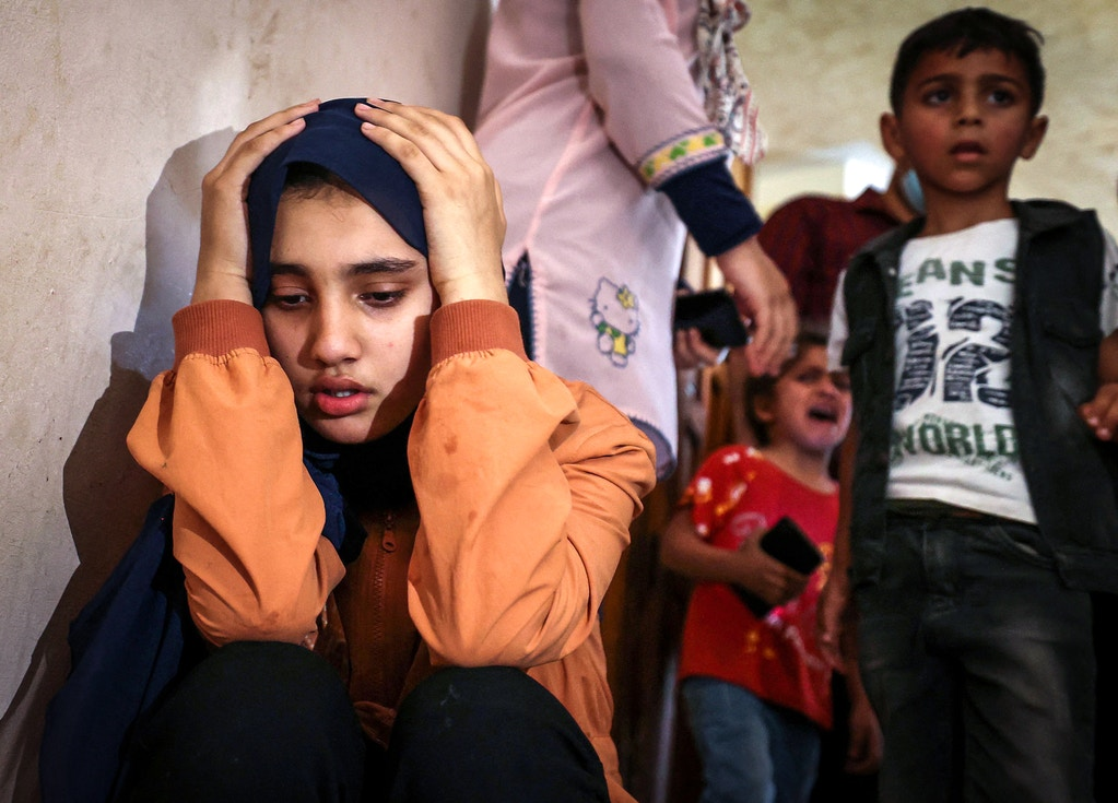 TOPSHOT - Relatives of Palestinian Hussien Hamad, 11, mourn during his funeral in Beit Hanoun in the northern Gaza Strip on May 11, 2021. - Israel and Hamas exchanged heavy fire, with 22 Palestinians killed in Gaza, in a dramatic escalation between the bitter rivals sparked by unrest at Jerusalem's flashpoint Al-Aqsa Mosque compound. Nine children were among those killed in the blockaded Gaza Strip that is controlled by the Islamist movement and 106 people there were wounded, local health authorities said. (Photo by MAHMUD HAMS / AFP) (Photo by MAHMUD HAMS/AFP via Getty Images)
