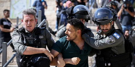 JERUSALEM - MAY 18: Israeli forces take a Palestinian into custody as Palestinians gathered in front of Jerusalem's Damascus Gate to protest against Israeli attacks on Gaza Strip, in East Jerusalem on May 18, 2021. Israeli forces assaulted and arrested Palestinians. (Photo by Mostafa Alkharouf/Anadolu Agency via Getty Images)