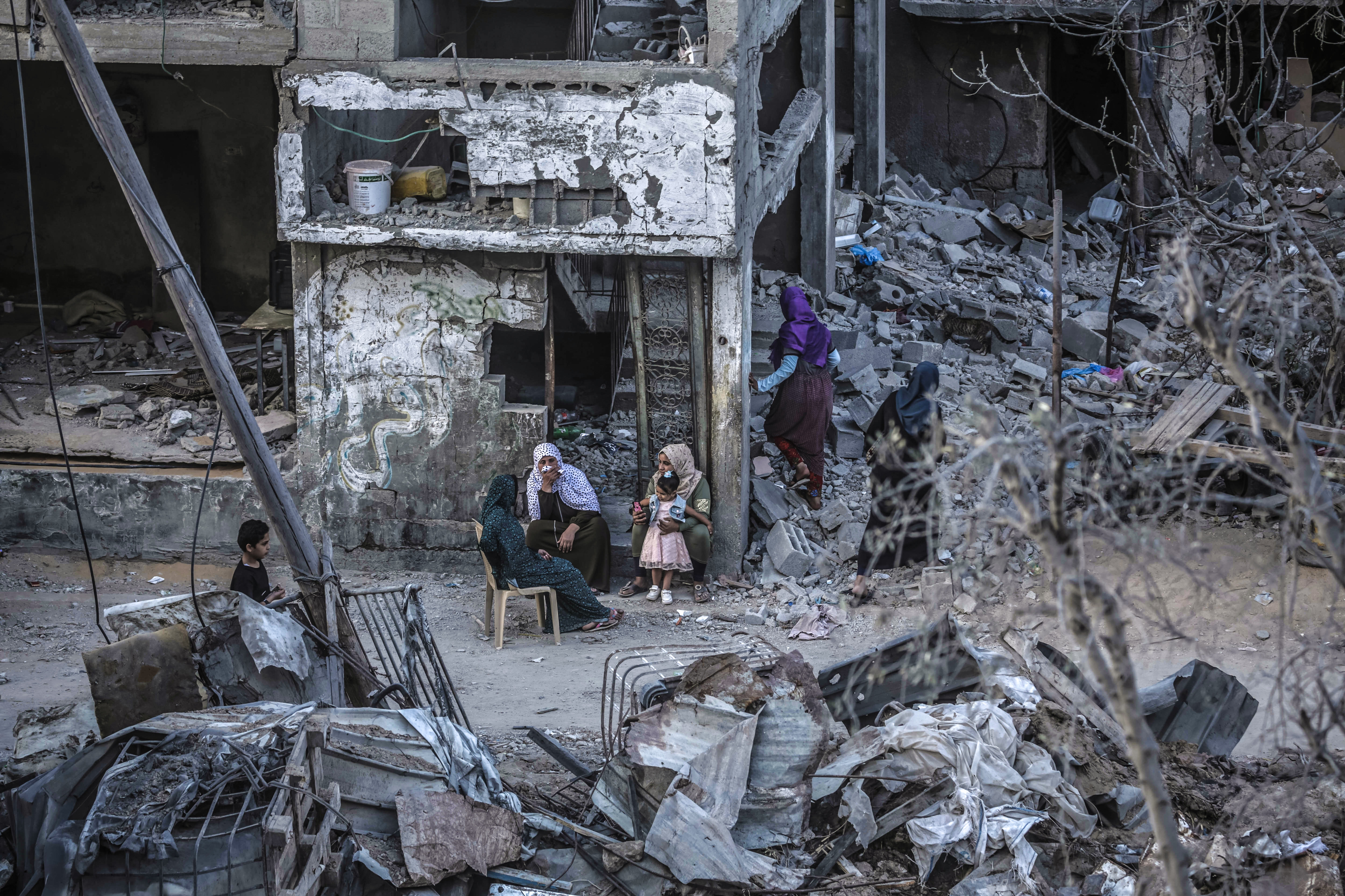 GAZA CITY, GAZA - MAY 22: Palestinians sit amongst the rubble of their destroyed houses after a ceasefire between Israel and Gaza fighters, in Beit Hanun, northern Gaza Strip, on May 22, 2021 in Gaza City, Gaza. The ceasefire between Israel and Hamas appeared to be holding, despite fresh clashes at Al-Aqsa Mosque in East Jerusalem. The ceasefire brings to an end eleven days of fighting which killed more than 250 Palestinians, many of them women and children, and 13 Israelis. The conflict began on May 10th after rising tensions in East Jerusalem and clashes at the Al Aqsa Mosque compound. (Photo by Fatima Shbair/Getty Images)