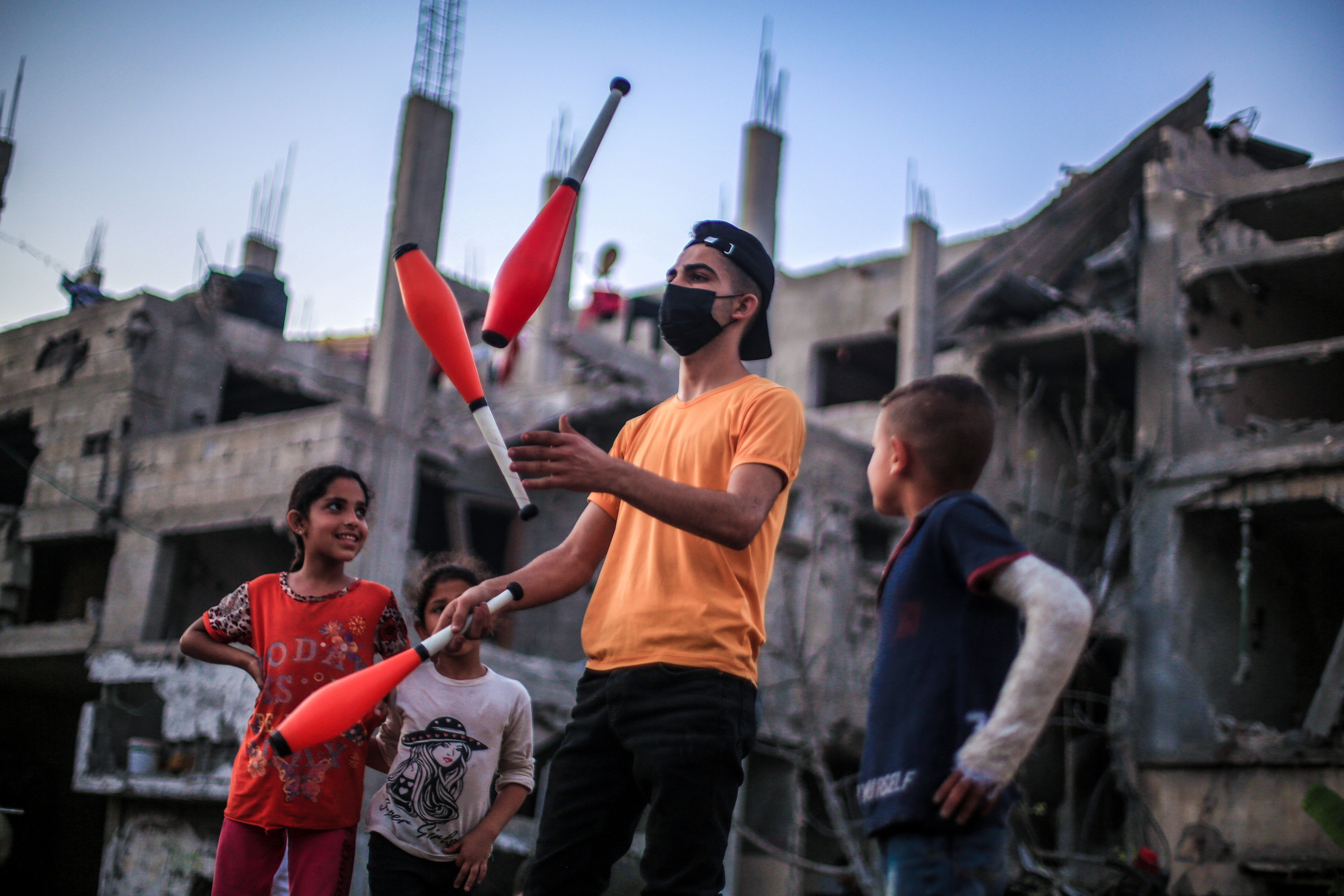 BEIT HANOUN, GAZA - MAY 25: Mohammad Recep, 17, plays to enjoy children on rubble of destroyed buildings targeted by Israeli attacks, in Beit Hanoun, Gaza on May 25, 2021. A ceasefire deal between Israel and Hamas was reached following 11 days of the worst fighting between the two sides in recent years. (Photo by Abed Zagout/Anadolu Agency via Getty Images)
