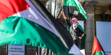 A man is seen waving the Palestinian flag during a Rally on May 22, 2021 in Melbourne, Australia.
