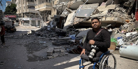 Gazan photojournalist Momen Faiz Quraiqea sits in front of the remains of his media agency's office that was destroyed by an Israeli airstrike in Gaza City on May 14, 2021.