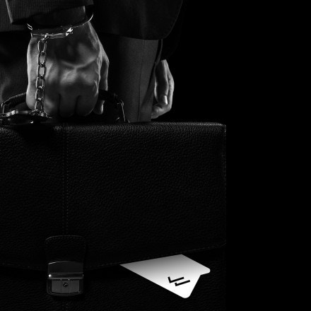 side view of businessman in handcuffs holding briefcase isolated on black