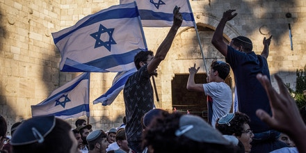 15 June 2021, Israel, Jerusalem: People gather at the Damascus Gate of the Old City of Jerusalem with flags of Israel during the controversial Flag March, organized by Israeli right-wing nationalists. Photo: Ilia Yefimovich/dpa (Photo by Ilia Yefimovich/picture alliance via Getty Images)