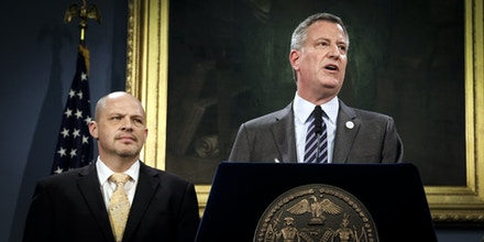 File - In this Thursday, May 1, 2014 file photo, Michael Mulgrew, left, President of the United Federation of Teachers listens as New York City Mayor Bill de Blasio speaks during a news conference at City Hall in New York. De Blasio is taking heat for soliciting contributions from deep-pocket donors with business interests before the city sparking a flurry of conflict-of-interest investigations that are threatening to taint his administration as one that revived pay-for-play politics in New York. (AP Photo/Seth Wenig)