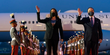 Vice President Kamala Harris waves with Guatemala's Minister of Foreign Affairs Pedro Brolo on arrival in Guatemala City, on June 6, 2021, at Guatemalan Air Force Central Command.