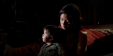 Fatima Flores, 17, holds her son Amilcar Cortez, 1, in their home in Armenia, El Salvador on May 21, 2021. His partner Jose Cortez, 20, and father of her 2 sons is missing since March 14, 2021. Fred Ramos for The Intercept