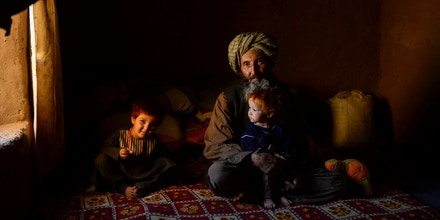 An internally displaced man sits with his children at a temporary home in a refugee camp on the outskirts of Herat on September 2,2020. (Photo by HOSHANG HASHIMI / AFP) (Photo by HOSHANG HASHIMI/AFP via Getty Images)