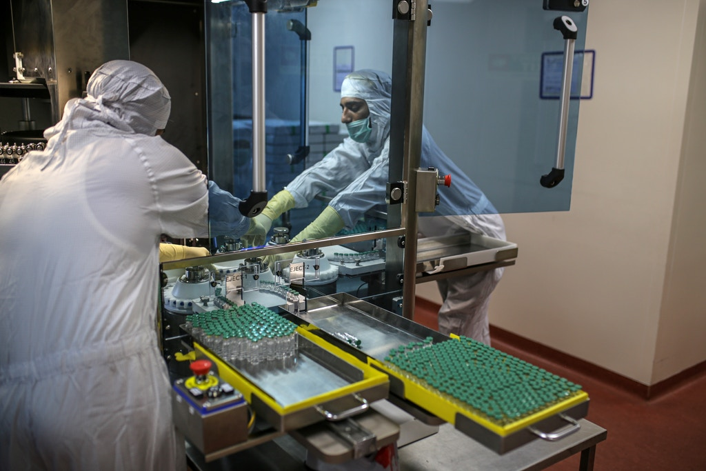 Employees work on the production of line for vials of Covishield, the local name for the Covid-19 vaccine developed by AstraZeneca Plc. and the University of Oxford, at the Serum Institute of India Ltd. Hadaspar plant in Pune, Maharashtra, India, on Friday, Jan. 22, 2021. Serum, which is the world's largest vaccine maker by volume, has an agreement with AstraZeneca to produce at least a billion doses. Photographer: Dhiraj Singh/Bloomberg via Getty Images