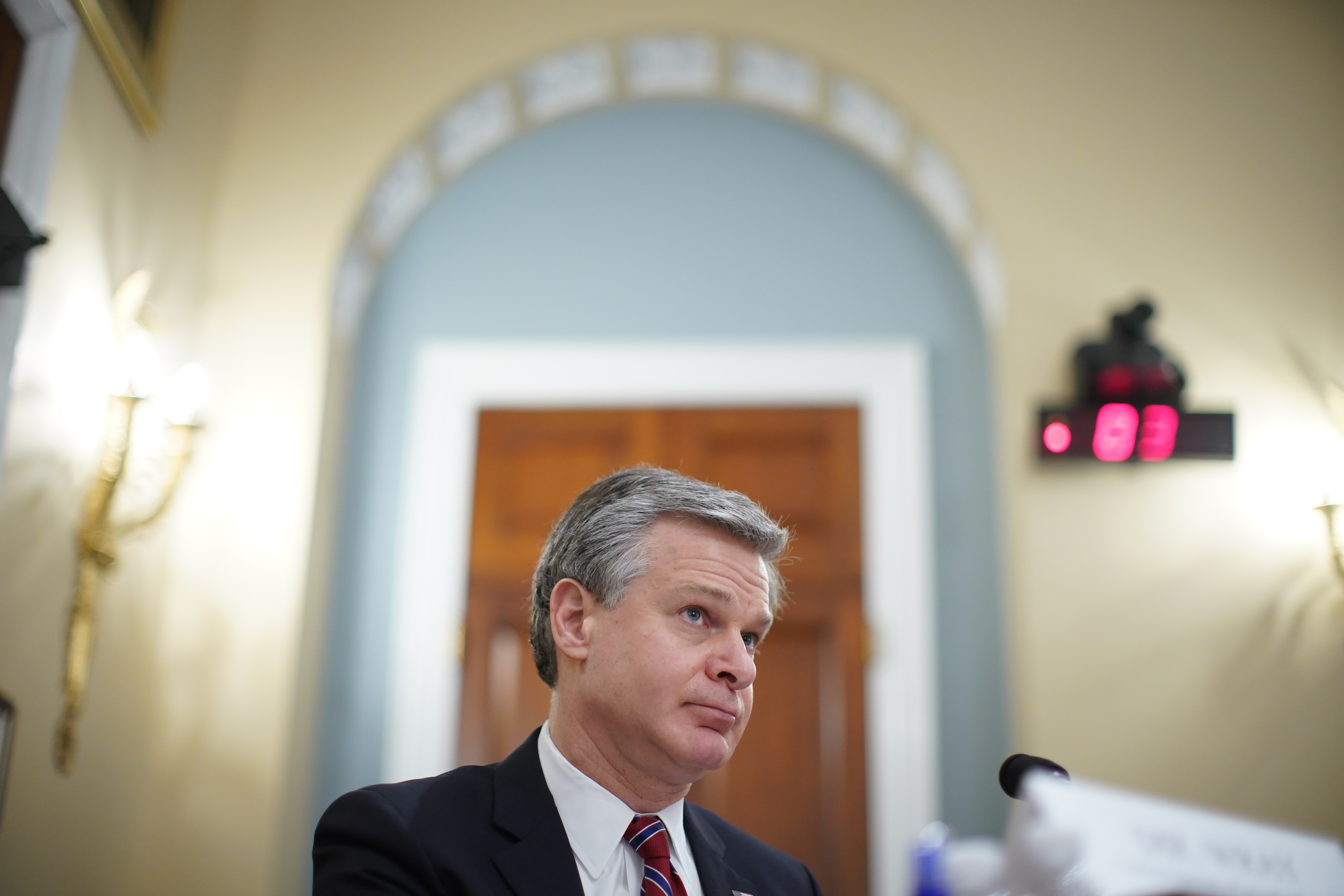 """Christopher Wray, director of the Federal Bureau of Investigation (FBI), pauses during a House Intelligence Committee hearing in Washington, D.C., U.S., on Thursday, April 15, 2021. The hearing follows the release of an unclassified report by the intelligence community detailing the U.S. and its allies will face """"a diverse array of threats"""" in the coming year, with aggression by Russia, China and Iran. Photographer: Al Drago/Bloomberg via Getty Images"""