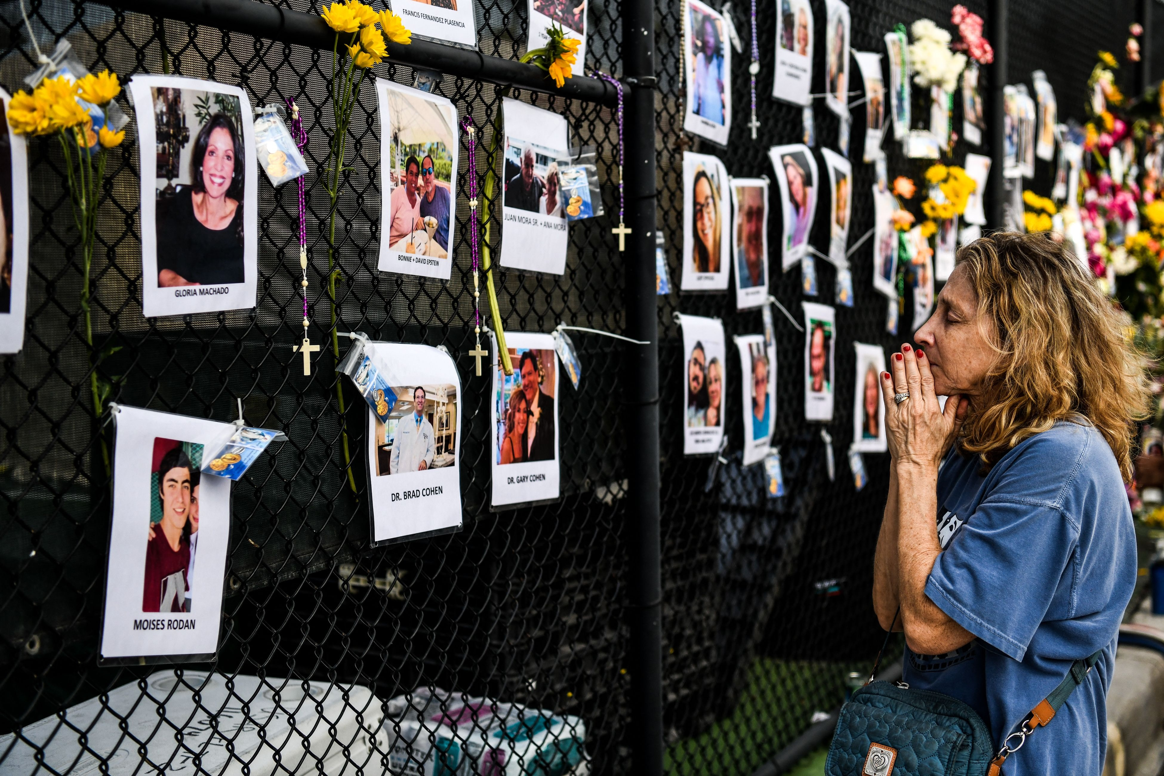 TOPSHOT - A woman prays in front of photos at the makeshift memorial for the victims of the building collapse, near the site of the accident in Surfside, Florida, north of Miami Beach on June 27, 2021. - The death toll after the collapse of a Florida apartment tower has risen to nine, officials said Sunday, with more than 150 people still missing and their weary families waiting more than three days afterwards for information as to their fate. The outlook grew more and more grim by the hour, however, as the slow rescue operation, involving workers sorting nonstop through the rubble in torrid heat and high humidity, carried on. (Photo by CHANDAN KHANNA / AFP) (Photo by CHANDAN KHANNA/AFP via Getty Images)
