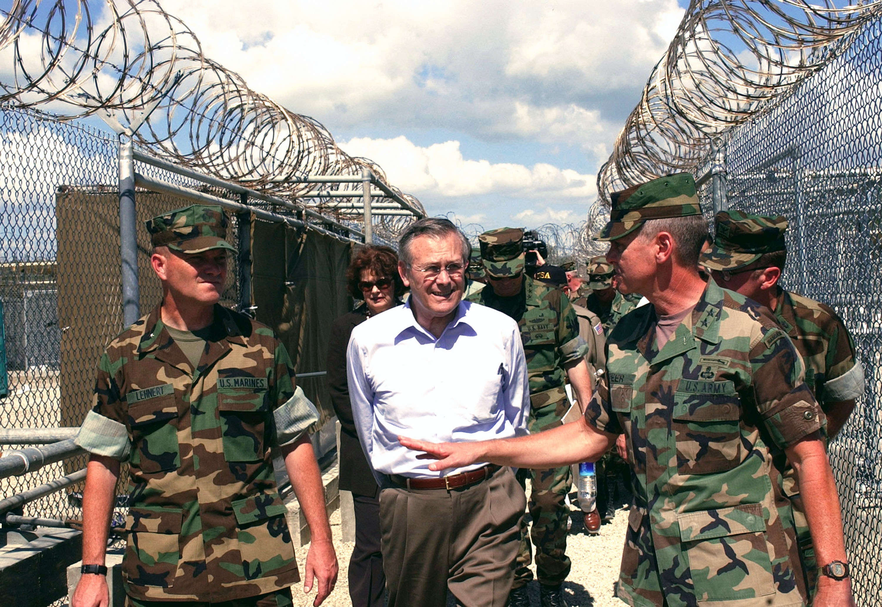 400243 01: U.S. Secretary of Defense Donald H. Rumsfeld (C) is greeted by BGen. Michael R. Lehnert, Joint Task Force-160 Commander (L) and MGen. Gary D. Speer, Assistant Commander in Chief, U.S. Southern Command (R) on a visit to Camp X-Ray January 27, 2002 at U.S. Naval Base Guantanamo Bay, Cuba. Rumsfeld said that the Taliban and al Qaeda prisoners being held at the base would not be given prisoner-of-war status. (Photo by Joshua S. Higgins/USMC/Getty Images)
