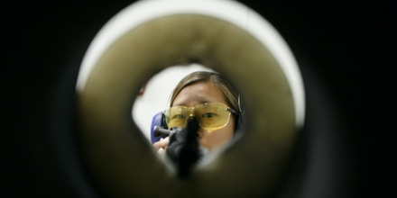 Forensic scientist trainee, Katie Carlson, fires an AK-47 assault rifle  into the bullet recovery tank at the Virginia State Forensics lab in Richmond, Va., Thursday, Jul. 17, 2008.  (AP Photo/Steve Helber)
