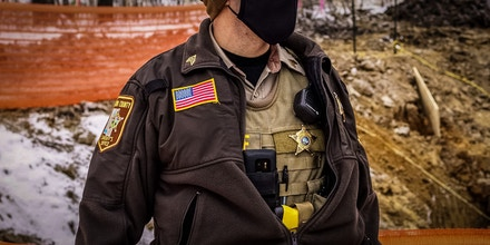 Aitkin County sheriff guards the construction site of the Line 3 oil pipeline after protesters were arrested near Palisade, Minnesota on January 9, 2021. - Line 3 is an oil sands pipeline which runs from Hardisty, Alberta, Canada to Superior, Wisconsin in the United States. In 2014, a new route for the Line 3 pipeline was proposed to allow an increased volume of oil to be transported daily. While that project has been approved in Canada, Wisconsin, and North Dakota, it has sparked continued resistance from climate justice groups and Native American communities in Minnesota. While many people are concerned about potential oil spills along Line 3, some Native American communities in Minnesota have opposed the project on the basis of treaty rights. (Photo by Kerem Yucel / AFP) (Photo by KEREM YUCEL/AFP via Getty Images)