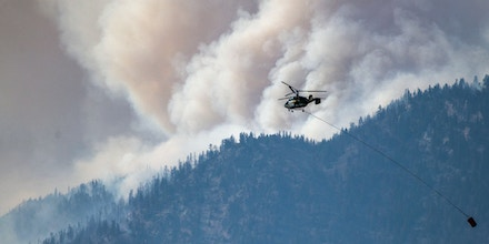 A helicopter prepares to make a water drop as smoke billows along the Fraser River Valley near Lytton, British Columbia, Canada, on July 2, 2021.