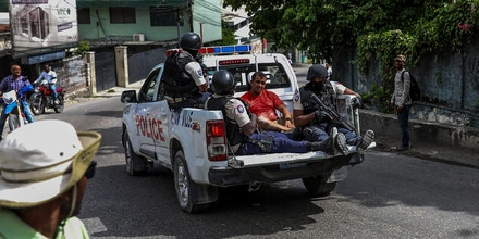 Two men, accused of being involved in the assassination of President Jovenel Moise, are being transported to the Petionville station in a police car in Port au Prince on July 8, 2021. - Police in Haiti have surrounded a group of possible suspects in the assassination of President Jovenel Moise, the UN envoy to Haiti said. Helen La Lime said from the Haitian capital that four members of a group that attacked the presidential palace Wednesday and shot the president have been killed by police and six others are in custody. (Photo by Valerie Baeriswyl / AFP) (Photo by VALERIE BAERISWYL/AFP via Getty Images)