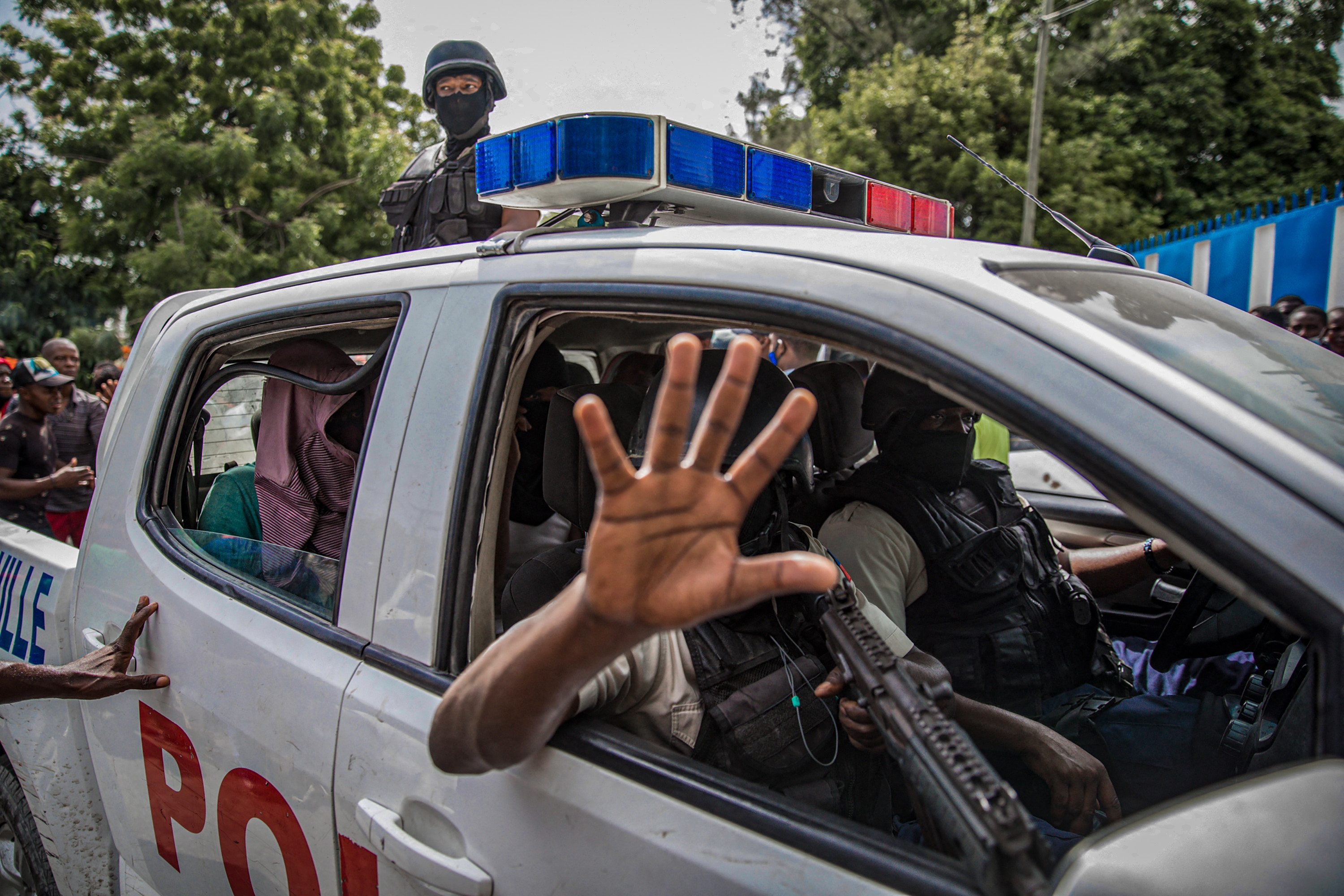 TOPSHOT - Two men, accused of being involved in the assassination of President Jovenel Moise, are being transported to the Petionville station in a police car in Port au Prince on July 8, 2021. - Police in Haiti have surrounded a group of possible suspects in the assassination of President Jovenel Moise, the UN envoy to Haiti said. Helen La Lime said from the Haitian capital that four members of a group that attacked the presidential palace Wednesday and shot the president have been killed by police and six others are in custody. (Photo by Valerie Baeriswyl / AFP) (Photo by VALERIE BAERISWYL/AFP via Getty Images)