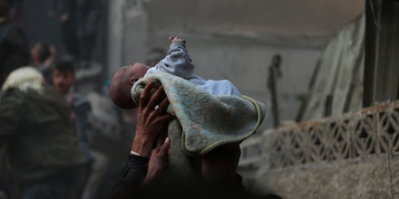 """A baby pulled from the rubble following an airstrike is lifted into the air by White Helmets and community members in Douma, Syria, on Jan. 7, 2014. """"I know the boy,"""" Bassam Khabieh told The Intercept. """"He was orphaned two years later. ... This is the war. It's too difficult for everybody. This book is for all those children."""""""