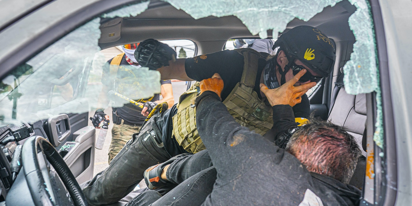 PORTLAND, OR - AUGUST 22: A member of the far-right group Proud Boys and a left-wing counter protester fight in a truck on August 22, 2021 in Portland, Oregon. The Proud Boys and other far-right extremists fought with anti-fascist activists in Portland on the anniversary of a similar fight in 2020.  (Photo by Nathan Howard/Getty Images)