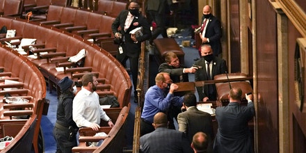 U.S. Capitol police officers point guns at a door during a joint session of Congress to count the votes of the 2020 presidential election takes place in the House Chamber in Washington, D.C., U.S., on Wednesday, Jan. 6, 2021. The U.S. Capitol was placed under lockdown and Vice President Mike Pence left the floor of Congress as hundreds of protesters swarmed past barricades surrounding the building where lawmakers were debating Joe Biden's victory in the Electoral College. Photographer: Stefani Reynolds/Bloomberg
