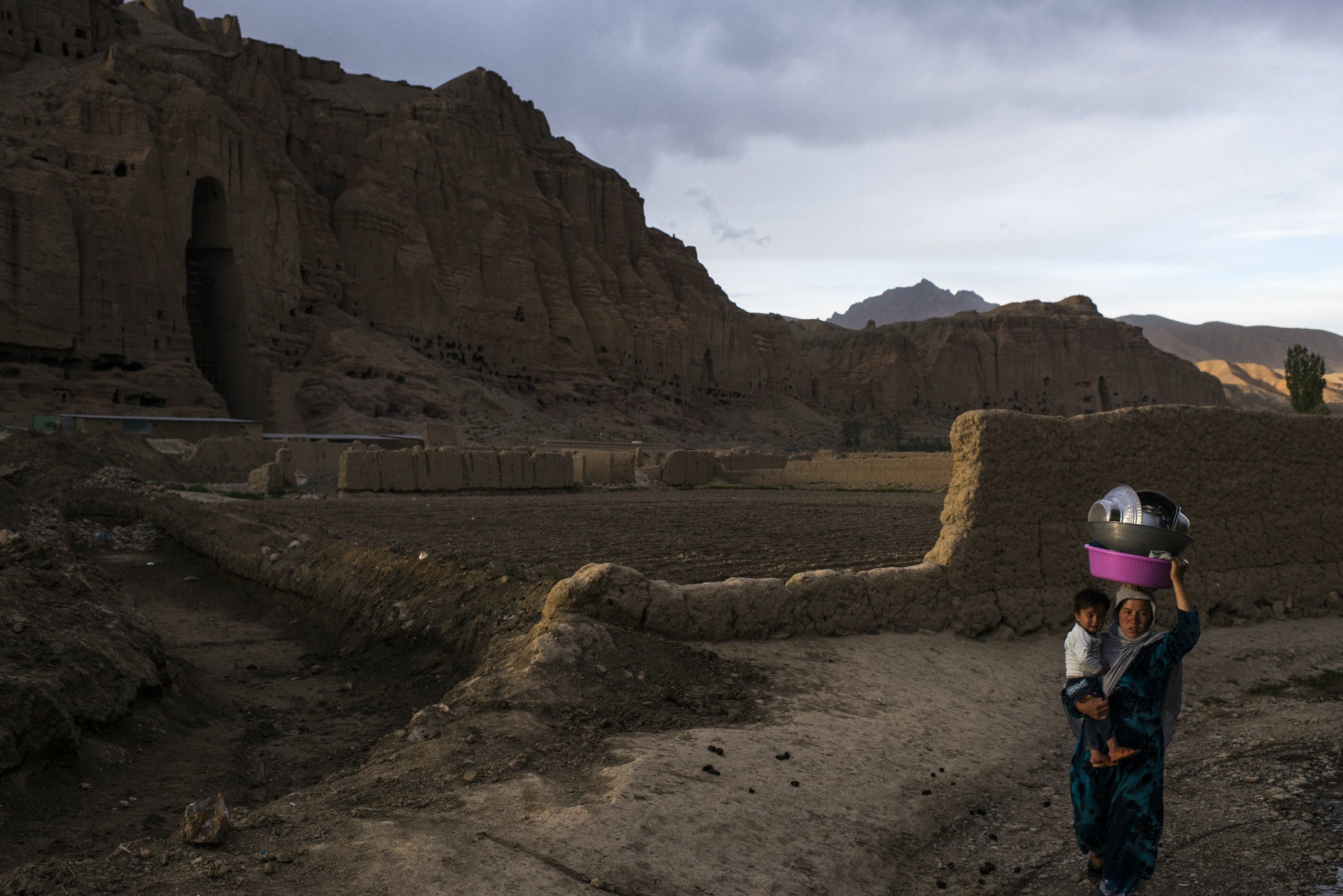 A woman carries a young child and crockery toward their nearby village after washing the utensils in a water spring near one of the famous, ancient Buddha niches carved out of the rock face looking over  Bamiyan City, the capital of central Afghanistan's Bamiyan province.