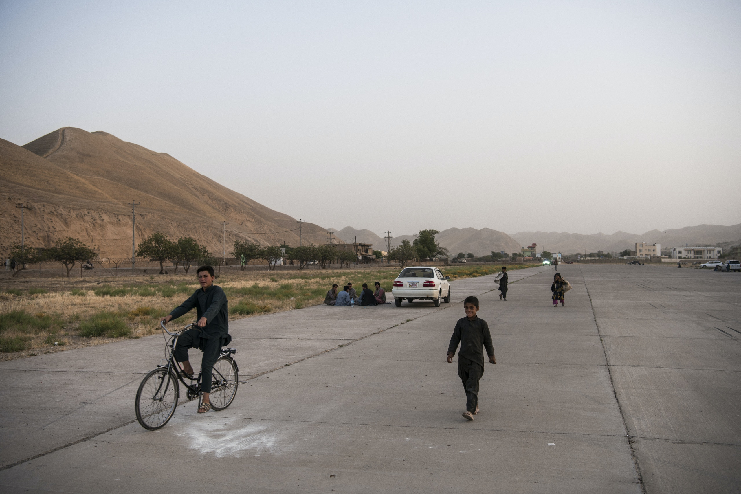 The runway at Qala-e-Naw airport, which is only used by military and humanitarian carriers nowadays and, when not in used, is open to resident of Qala-e-Naw, who use it as a setting for picnics in the afternoons, especially on the weekends. In recent weeks, as the Taliban has pushed closer toward Qala-e-Naw from outlying districts, residents who used to picnic on the city's outskirts and other districts are staying closer to home for such leisure activities. The runway is one such place being utilised.